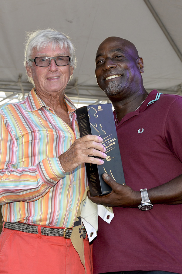Two veteran sporting icons from Antigua: Sir Viv Richards presents Biwi Magic owner, Geoffrey Pidduck with  Johnnie Walker prizes for first place on the Johnnie Walker Race Day 2 at Antigua Sailing Week - Credit: Ted Martin/Photofantasyantigua.com